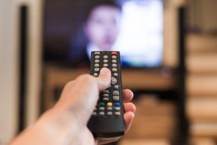 テレビに向かってリモコンを向ける人